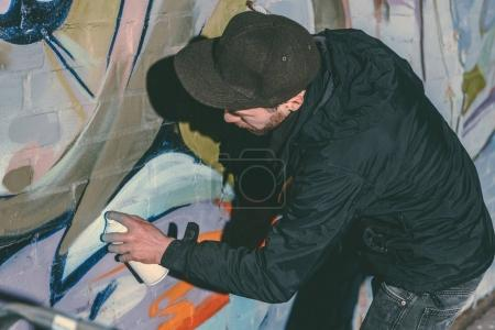 street artist painting colorful graffiti on wall of building at night