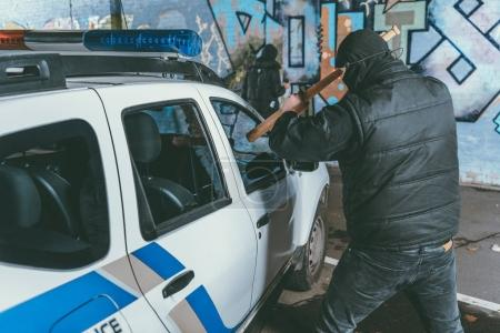 vandal crashing police car with baseball bat while another man painting graffiti on wall