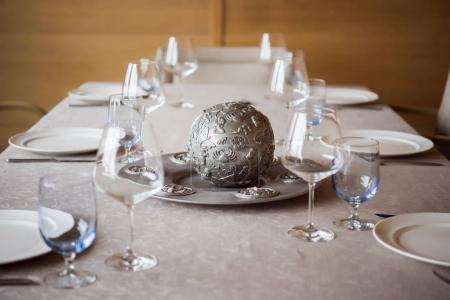 Photo for Close up view of arrangement of cutlery, decorations and empty wineglasses on table in restaurant - Royalty Free Image