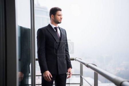 Porträt eines nachdenklichen jungen Mannes im Anzug, der auf dem Balkon steht