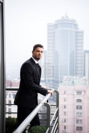 portrait of young pensive man in suit standing at restaurant balcony