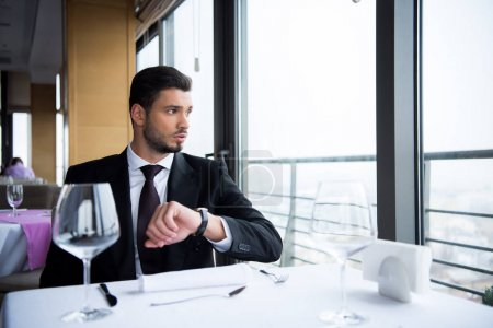 portrait of man in suit looking out window while sitting at served table in restaurant