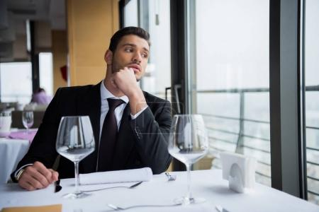 Photo for Pensive man in suit looking away while waiting for order in restaurant - Royalty Free Image