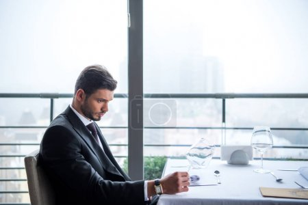 pensive man in suit looking away while waiting for order in restaurant