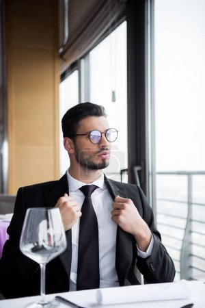 pensive man in suit and eyeglasses looking away while waiting for order in restaurant