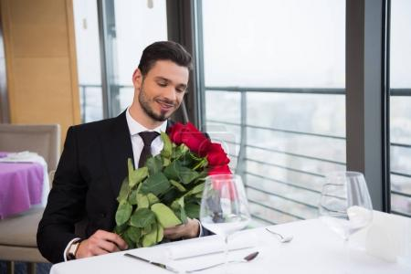 smiling man in suit with bouquet of red roses waiting for girlfriend in restaurant