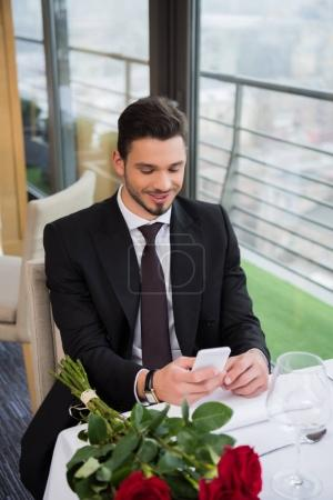 portrait of smiling man in suit using smartphone while waiting for girlfriend in restaurant