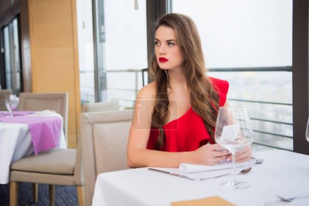 portrait of beautiful woman with smartphone looking away while waiting for boyfriend in restaurant