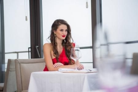 portrait of smiling attractive woman in red dress sitting at table in restaurant