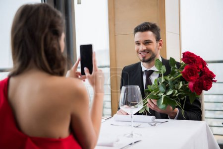 partial view of girlfriend taking picture of smiling boyfriend with bouquet of roses in restaurant during romantic date