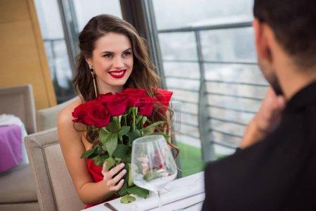 Photo pour Femme souriante avec bouquet de roses lors d'un rendez-vous romantique avec petit ami au restaurant, Saint Valentin - image libre de droit