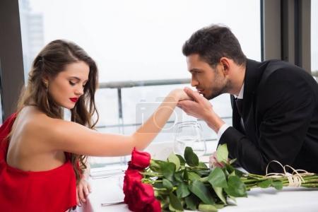Photo pour Vue latérale de l'homme embrasser copines main pendant la date sur st Saint-Valentin dans le restaurant - image libre de droit