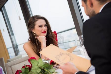 Photo pour Femme souriante regardant petit ami pendant la St Valentin date dans le restaurant - image libre de droit