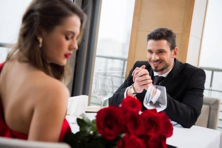 Photo for Selective focus of smiling man looking at girlfriend with bouquet of flowers in restaurant, st valentine day - Royalty Free Image