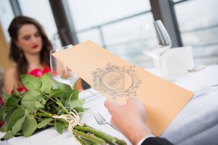 Photo pour Mise au point sélective de couple avec menu assis à table st-valentin au restaurant - image libre de droit