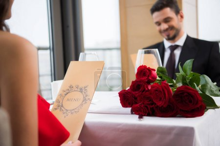 selective focus of couple reading menu on romantic date in restaurant on st valentine day