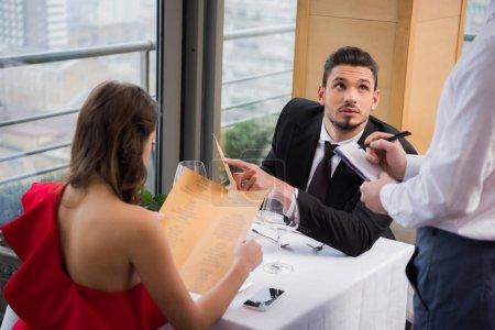 Photo pour Mise au point sélective de l'homme rend l'ordonnance st-valentin romantique date avec petite amie au restaurant - image libre de droit