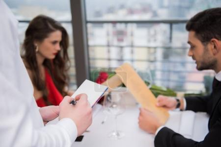 Photo for Selective focus of waiter writing down visitors order in restaurant - Royalty Free Image