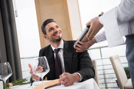 partial view of smiling man looking at waiter with bottle of wine in restaurant
