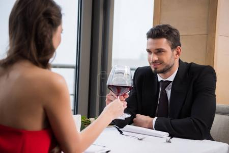 partial view of couple clinking glasses of red wine during romantic date in restaurant on st valentine day
