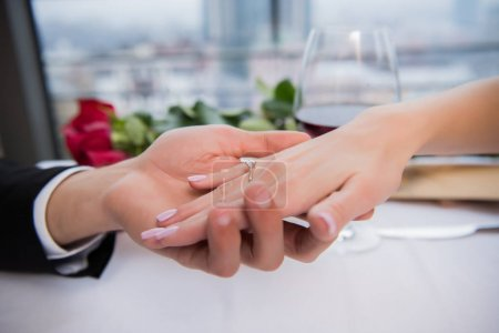 Photo for Cropped shot of boyfriend holding fiances hand during romantic date in restaurant - Royalty Free Image