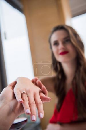 selective focus of man holding fiances hand with wedding ring on finger