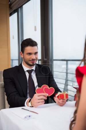 partial view of young man presenting gift to girlfriend on romantic date in restaurant
