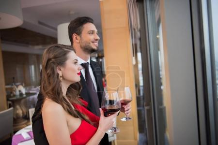 couple with glasses of red wine celebrating st valentine day in restaurant