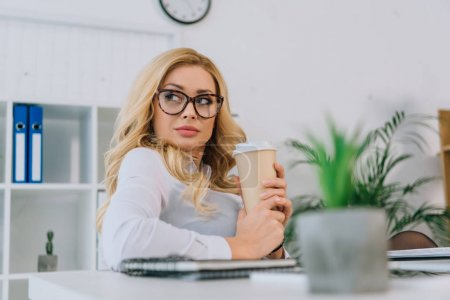 Photo for Seductive businesswoman holding coffee in paper cup - Royalty Free Image