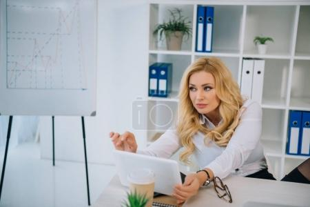 businesswoman taking selfie at working place with tablet