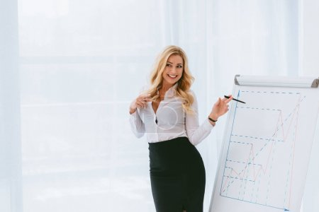 smiling seductive businesswoman showing something at chart