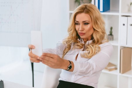 sexy businesswoman taking selfie at working place with smartphone