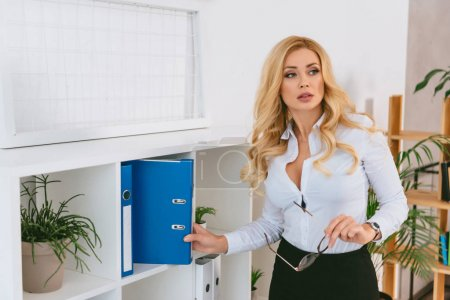 seductive woman taking folder from shelf