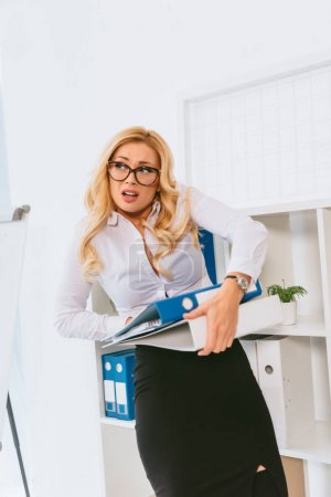 exhausted businesswoman holding folders with documents in office