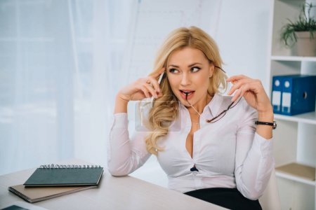 attractive sexy businesswoman talking by smartphone in office and biting glasses