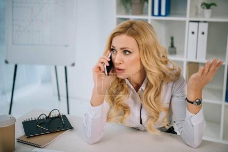 irritated businesswoman talking by smartphone in office