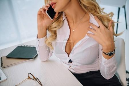 cropped image of sexy woman with decollete talking by smartphone