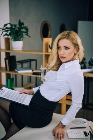 attractive sexy woman sitting on table and holding documents