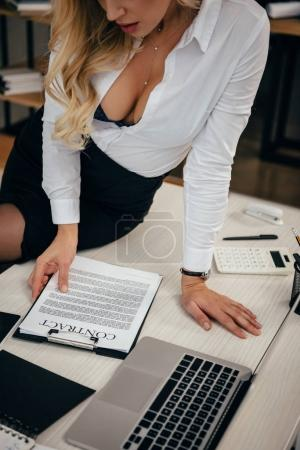 cropped image of seductive woman sitting on table and reading working contract