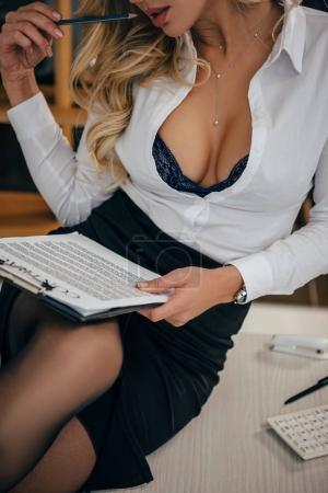 cropped image of sexy woman sitting on table and reading documents