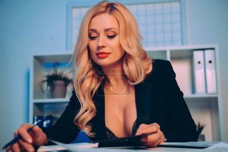 Photo for Blonde sexy woman with decollete reading something at office - Royalty Free Image