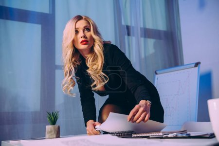 sexy businesswoman with knee on table stapling papers with stapler and looking away