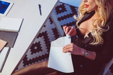 cropped image of sexy woman stapling papers with stapler