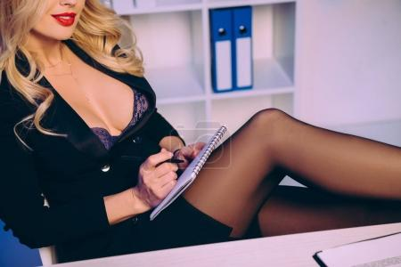 cropped image of sexy woman with naked chest sitting with notebook and pen