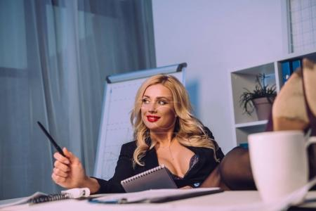 Photo for Sexy woman with naked chest sitting with legs on table and holding notebook - Royalty Free Image