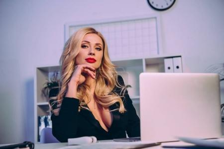 seductive woman working with laptop in office and looking at camera