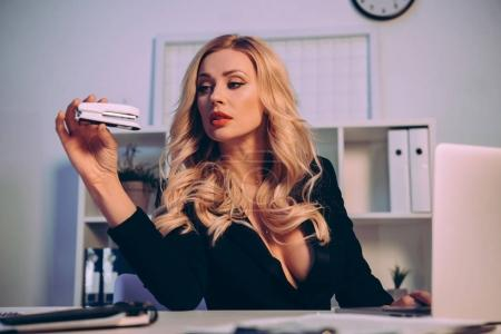 sexy woman with decollete looking at stapler at table