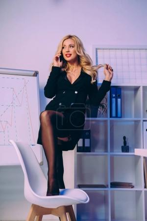 sexy woman putting leg on chair and talking by smartphone