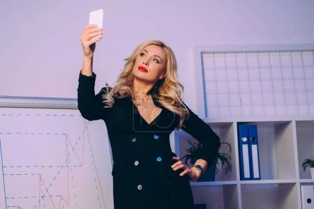 seductive woman taking selfie with smartphone near diagram chart