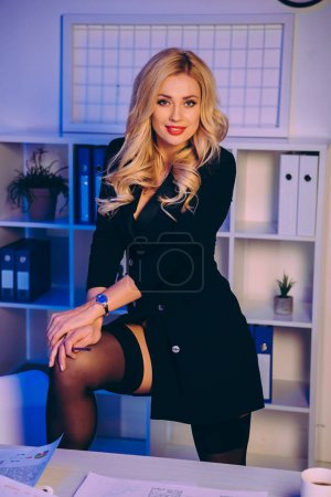 smiling sexy woman putting leg on chair in office and looking at camera